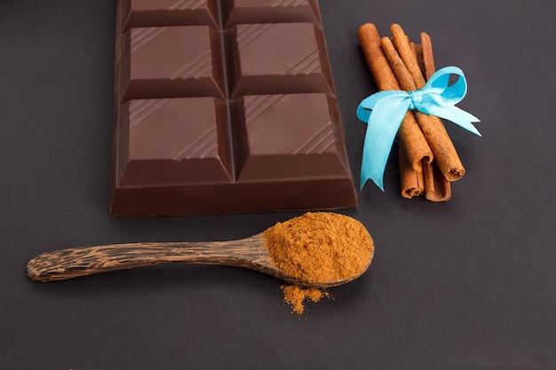 Barra de chocolate, rolos de canela, colher de pau de canela