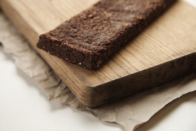 Barra de chocolate saudável artesanal recém-assada orgânica com frutas e nozes moídas na placa de madeira e papel ofício, isolada na mesa branca