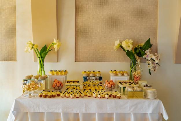 Barra de chocolate. uma mesa festiva com panakota, macarons, muffins, merengues e com dois vasos