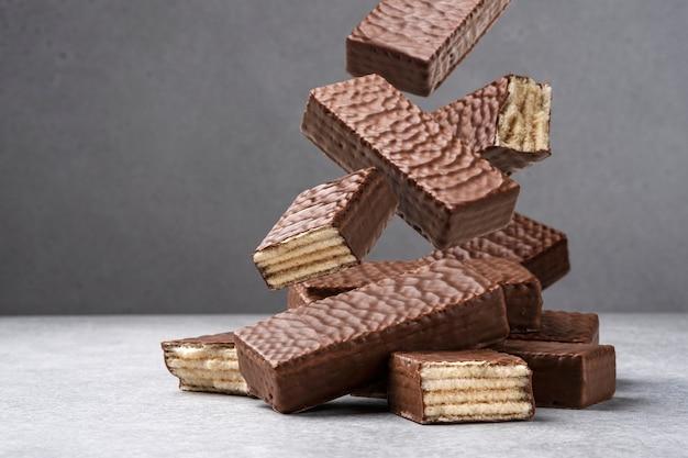 Barra de chocolate waffle caindo em fundo cinza