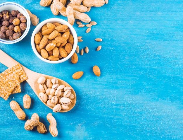 Barra de energia feita com amêndoa; amendoim; pistache; avelãs e sementes em fundo azul