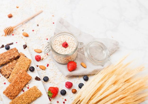 Barra de granola de cereais orgânicos com bagas na placa de mármore com colher de mel e pote de aveia e toalha de linho na mesa de mármore.