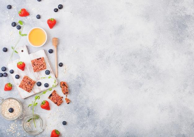 Barra de granola de cereais orgânicos com bagas na placa vintage com colher de mel e pote de aveia na mesa de mármore. morango, framboesa e mirtilo com folhas de hortelã