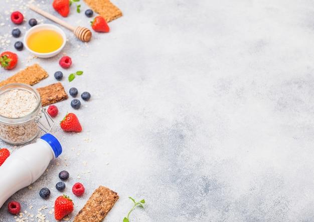 Barra de granola de cereais orgânicos com frutas com colher de mel e pote de aveia e garrafa de bebida de leite. vista do topo. morango, framboesa e mirtilo com nozes amêndoas.