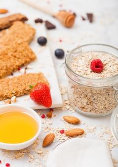 Barra de granola de cereais orgânicos com frutas na placa de mármore com colher de mel e pote de aveia e coco na mesa de mármore.