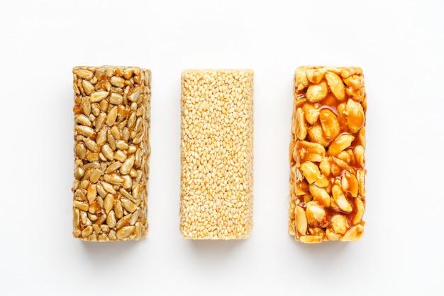 Barra de granola de grão com amendoim, gergelim e sementes em uma fileira. vista superior, três, sortido, barras, isolado