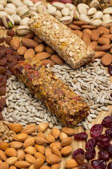 Barra de granola de proteína balanceada. nozes, sementes, cereais em fundo de madeira.
