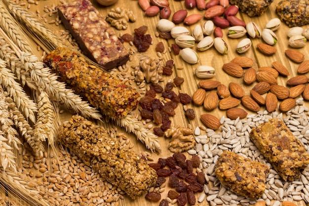 Barra de granola de proteína balanceada. nozes, sementes, cereais, espigas de trigo. comida vegetariana de dieta saudável. vista do topo. superfície de madeira. fechar-se