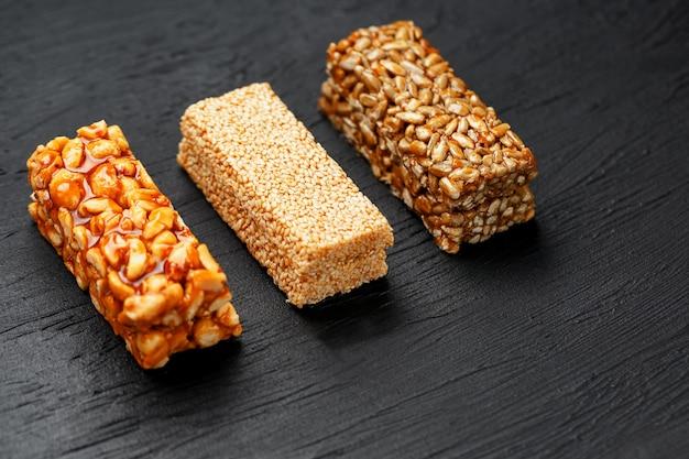 Barra de granola do cereal com sementes dos amendoins, do sésamo e de girassol em uma placa de corte em uma tabela de pedra escura. vista de cima. três barras sortidas