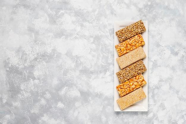 Barra de granola. lanche saudável sobremesa doce. gergelim, amendoim, girassol em mel. gozinaki é comida nacional da geórgia, doce oriental. vista superior em concreto
