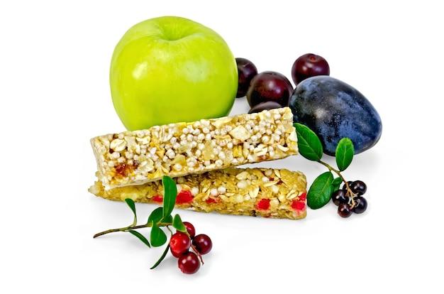 Barra de granola, maçã verde, ameixa, cereja, ramos com folhas e bagas de mirtilo isoladas no fundo branco