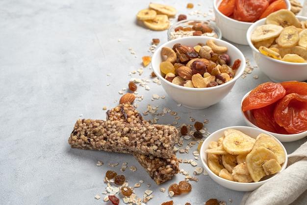 Barra de granola, nozes e frutas secas em tigelas sobre fundo de mármore branco