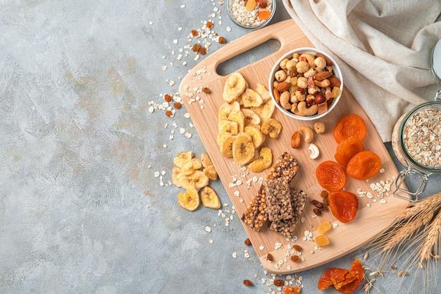 Barra de granola, nozes e frutas secas em uma tábua de madeira sobre fundo de mármore cinza claro