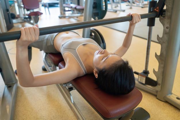Barra de levantamento da mulher, trabalhando com barra e seus braços e peito no ginásio.