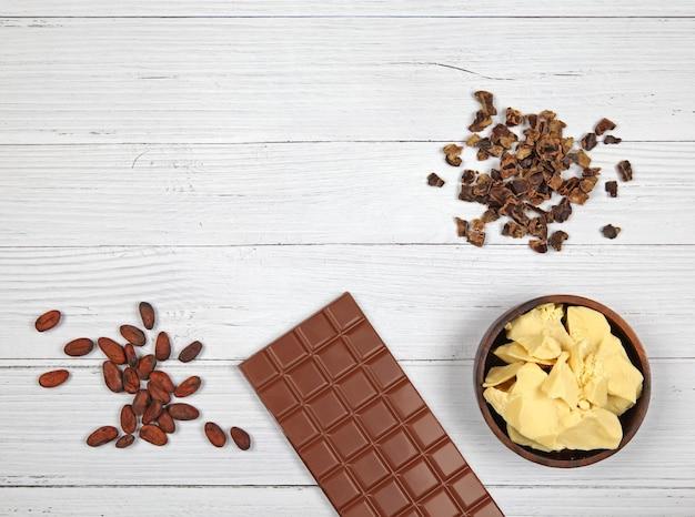 Barra de manteiga de cacau de alfarroba com chocolate ao leite e grãos de cacau em fundo de madeira claro