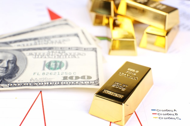 Barra de ouro com dinheiro na mesa close-up