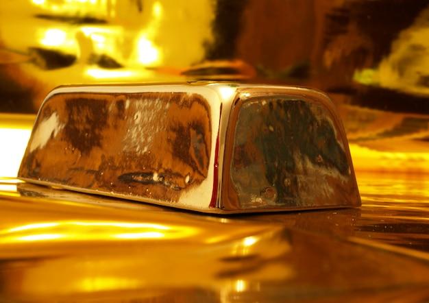 Barra de ouro do banco em uma superfície de ouro