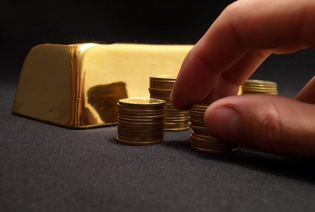Barra de ouro e moedas em um preto