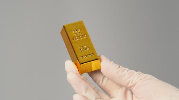 Barra de ouro na mão e usar luva de látex isolada em fundo cinza