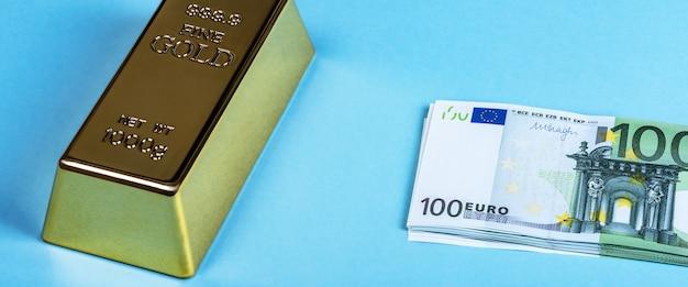 Barra de ouro, ouro, lingote e notas de euro em embalagem de dinheiro em um azul