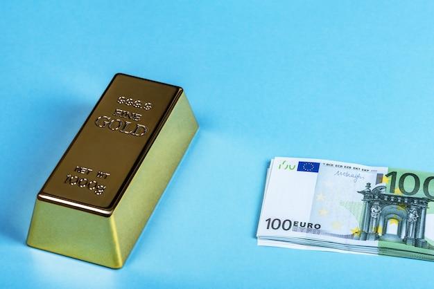 Barra de ouro, ouro, lingote e notas de euro em embalagem de dinheiro em um fundo azul.