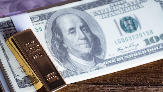 Barra de ouro sobreposição de dinheiro dólares no chão de madeira