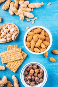 Barra de proteínas saudáveis feita com frutos secos; amendoins e avelãs no fundo azul textura
