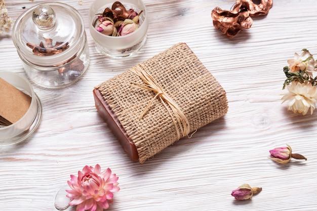 Barra de sabão caseiro envolto em tecido de cânhamo em fundo madeira