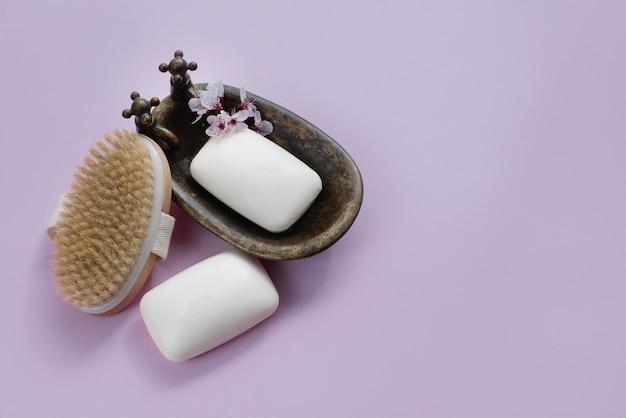 Barra de sabão e pincéis naturais na parede lilás. corpo de spa e conceito de cuidados de beleza