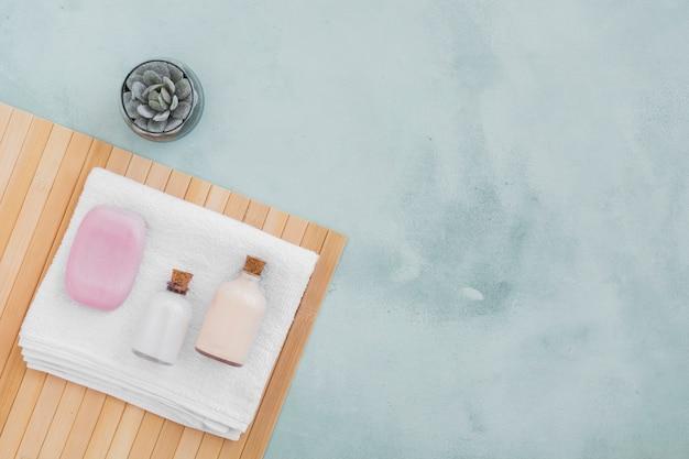 Barra de sabão e produtos de banho na toalha com espaço de cópia