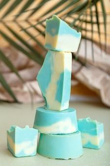 Barra de xampu sólida com muitas barras de sabonete artesanal natural de hortelã azul em formato de torre. sabonete orgânico de coco, produtos cosméticos de beleza para banho, para os cabelos, corpo e bem-estar com folhas de palmeira.