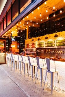 Barra decorada moderna do contador da torneira da cerveja com lugares vazios na noite.