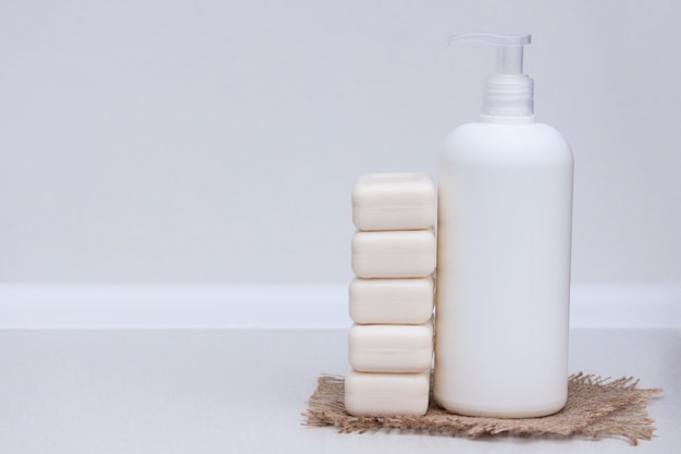 Barra do líquido e do sabão no fundo branco. espaço da cópia