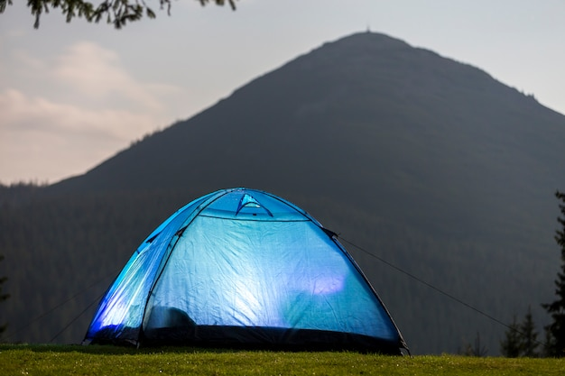Barraca azul na clareira da floresta no fundo distante da montanha.