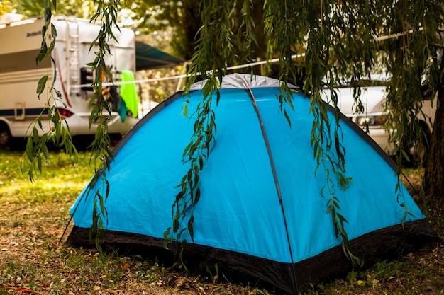 Barraca azul na sombra de uma árvore para acampar