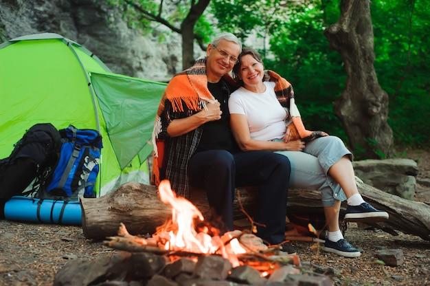 Barraca de acampamento casal romântico sentado à noite da fogueira