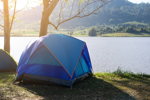 Barraca de acampamento perto do lago com luz solar bonita na manhã