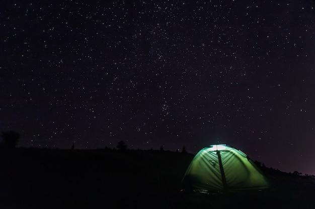 Barraca de acampamento turístico com luz dentro sob o céu estrelado