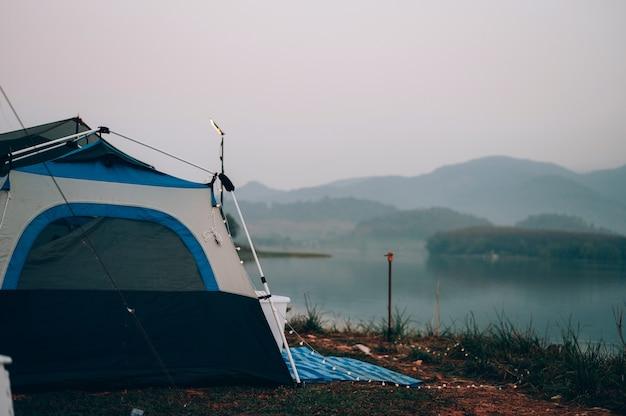 Barraca de camping na área de camping perto do lago entre montanha e nevoeiro