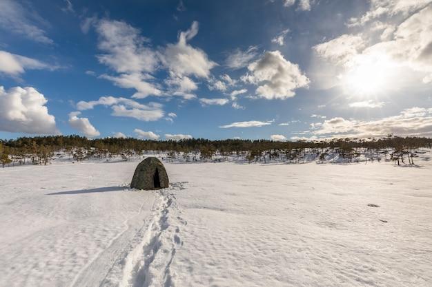 Barraca de camuflagem em um pântano coberto de neve com céu nublado
