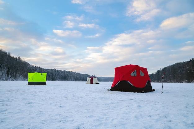 Barraca de pesca no gelo em um lago congelado ao pôr do sol. acampamento de pescadores em uma noite tranquila de inverno.