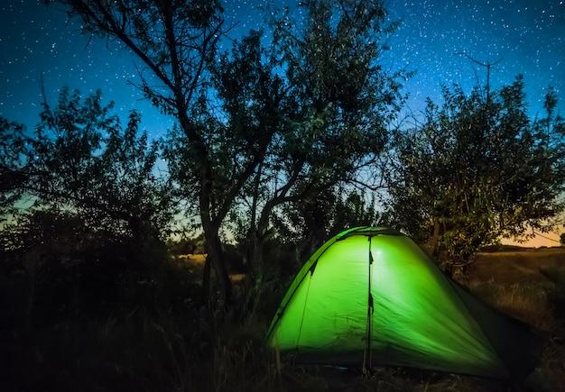 Barraca do turista brilhante sob céu estrelado