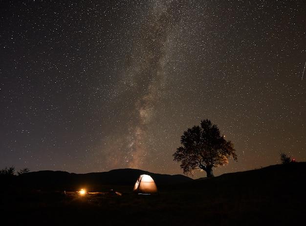 Barraca do turista e fogueira acesa no vale verde, sob o céu escuro e estrelado.