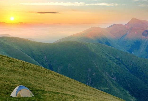 Barraca do turista localizada nas montanhas de verão ao pôr do sol. caminhadas acampamento na natureza à noite. viajar e fugir conceito.