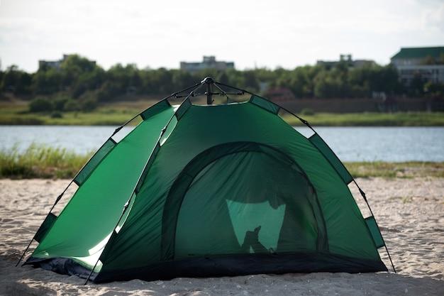 Barraca do turista na margem arenosa contra o fundo do rio. acampar descanso fora da cidade.