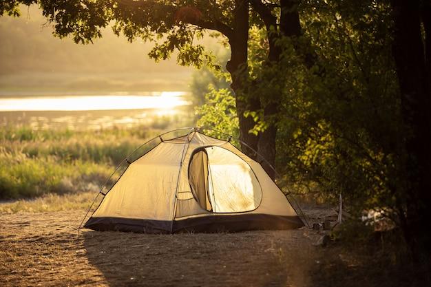Barraca do turista no rio e a floresta ao pôr do sol
