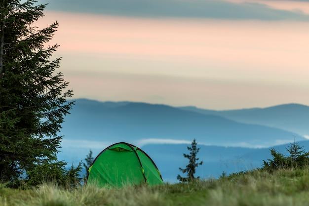 Barraca do turista pequeno na colina da montanha gramada. verão acampar nas montanhas ao amanhecer. conceito de turismo.