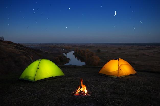 Barraca laranja e verde à beira do rio à noite
