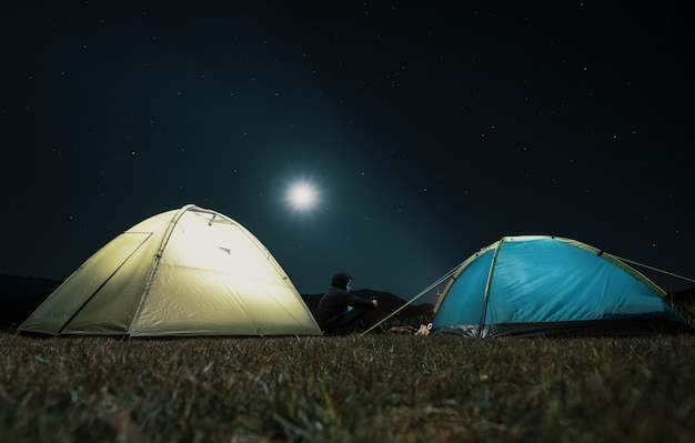 Barracas de turista no acampamento entre prado nas montanhas à noite
