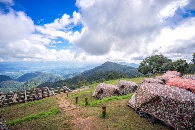 Barracas em acampar entre prado com bela paisagem nas montanhas sob o céu e clou